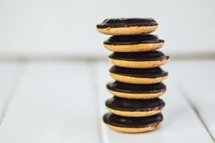 Ciastko sterta na białym drewnianym tle Round ciastka w czekoladowym glazerunku Stojaki na each inny Obraz Stock