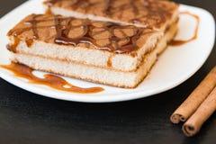 Ciastko tort z karmelu syropem na bielu talerzu z cynamonowymi kijami na drewnianym tle, Zdjęcie Stock