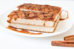 Ciastko tort z karmelu syropem na bielu talerzu z cynamonowymi kijami na drewnianym tle, Obrazy Stock