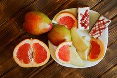 Ciastko zasycha i plasterki bonkreta i grapefruitowy w bia?ym talerzu na drewnianej powierzchni sosnowe deski Bufet w autentyczny obraz stock