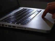 Cibercrime - um dedo no teclado do trackpad Fotografia de Stock Royalty Free