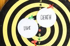 Cible avec des dards au centre dont l'inscription vivante et la mort photographie stock libre de droits