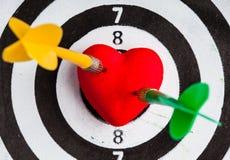 Cible blanche noire avec deux dards dans le symbole d'amour de coeur comme boudine Photo stock