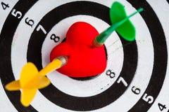 Cible blanche noire avec deux dards dans le symbole d'amour de coeur comme boudine Image stock