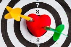 Cible blanche noire avec deux dards dans le symbole d'amour de coeur comme boudine Photos stock