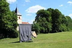 Cible pour le tir d'arc avec l'église du ` s de Vierge Marie derrière sur le palais Kratochvile Photographie stock