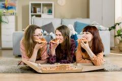 Cibo degli alimenti a rapida preparazione Tre bei amici felici che ridono, mangiando il partito della pizza a casa Donne cenando  fotografia stock libera da diritti