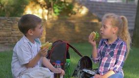 Cibo dei bambini con i panini in loro mani durante tempo e la conversazione del pranzo che si siedono sul prato inglese in cortil video d archivio