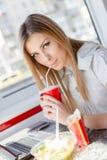 Cibo del lavoro: chiuda sul ritratto di bere & del cibo della ragazza bionda sveglia giovane bella della donna di affari diverten Fotografie Stock