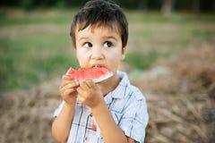 Cibo dell'anguria sugosa Bambino felice nel campo Umore di estate fotografia stock libera da diritti