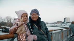 Cibo della bambina caldo durante la camminata sull'argine della città con la madre stock footage