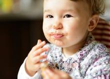 Cibo della neonata allegra con il fronte sudicio fotografie stock
