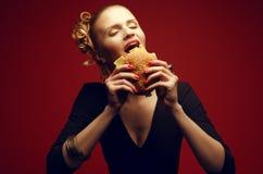 Cibo non sano Concetto degli alimenti industriali Piacere colpevole Donna che mangia hamburger Fotografia Stock Libera da Diritti
