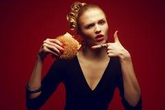 Cibo non sano Concetto degli alimenti industriali Piacere colpevole Donna con l'hamburger Fotografia Stock