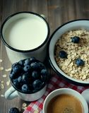 Cibo sano, alimento e concetto di dieta - farina d'avena saporita con le bacche e una tazza di latte e di una tazza di caffè Vist immagine stock libera da diritti