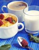 Cibo sano, alimento e concetto di dieta - fiocchi di granturco con le bacche, il latte ed il caffè per il fondo di legno blu dell fotografie stock