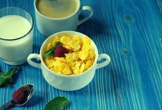 Cibo sano, alimento e concetto di dieta - fiocchi di granturco con le bacche, il latte ed il caffè per il fondo di legno blu dell immagine stock