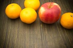 Cibo sano, mandarini, mela rossa, su una tavola di legno marrone Immagini Stock Libere da Diritti
