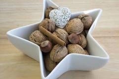 Cibo sano, nocciole varie in una ciotola bianca, tavola a forma di stella e di legno, decorazione di Natale fotografia stock