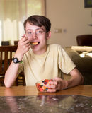 Cibo sano - ragazzo che mangia frutta Immagine Stock