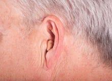 Cic gehoorapparaat in het oor stock foto's