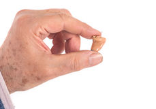 CIC hearing aid between fingers Stock Photos