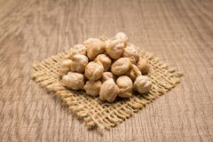 Chickpeas legume. Grains on square cutout of jute. Wooden table. Stock Photos