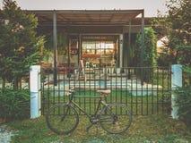 30 - Ciclagem da bicicleta estacionada na frente da casa do estilo do sótão fotos de stock royalty free