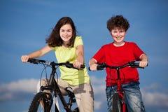Ciclagem da menina e do menino Foto de Stock