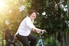 Ciclismo asiatico anziano della donna fotografia stock