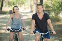 Ciclismo atlético de sorriso dos pares na floresta foto de stock