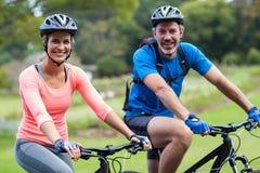 Ciclismo atlético dos pares na estrada imagens de stock