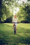 Ciclismo biondo della ragazza fotografia stock