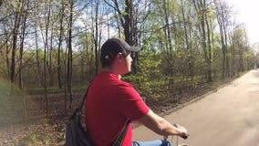 Ciclismo considerável do homem novo através do parque ensolarado no dia do ` s do verão Movimento lento da câmera da ação filme