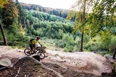 Ciclismo da equitação do motociclista da montanha na floresta do outono Fotos de Stock