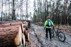 Ciclismo da equitação do motociclista da montanha na floresta molhada do outono Imagem de Stock