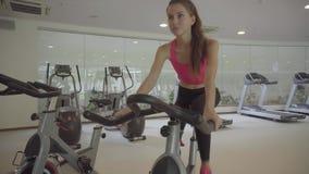 Ciclismo da jovem mulher na bicicleta de exercício no gym vídeos de arquivo