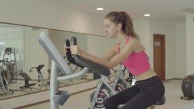 Ciclismo da jovem mulher na bicicleta de exercício no gym filme