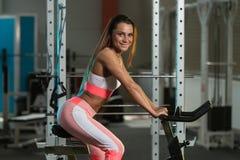 Ciclismo da jovem mulher no treinamento do halterofilismo da bicicleta Fotos de Stock Royalty Free