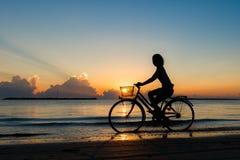 Ciclismo da menina no mar durante o nascer do sol Fotos de Stock Royalty Free