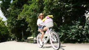 ciclismo da menina no parque da cidade no dia ensolarado video estoque