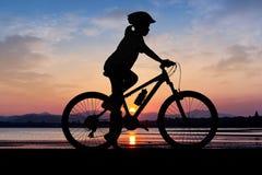 Ciclismo da menina no tempo do crepúsculo da praia Imagens de Stock