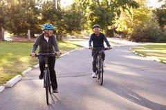 Ciclismo de Front View Of Senior Couple através do parque junto Foto de Stock Royalty Free