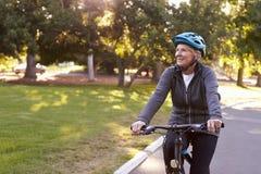 Ciclismo de Front View Of Senior Woman através do parque Fotografia de Stock Royalty Free