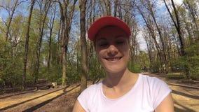 Ciclismo de sorriso alegre feliz da jovem mulher sob árvores no parque ensolarado Câmera da ação do POV vídeos de arquivo
