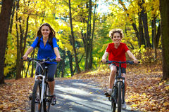 Ciclismo del ragazzo e dell'adolescente sulle tracce della foresta Fotografie Stock
