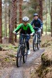 Ciclismo del ragazzo e dell'adolescente sulle tracce della foresta Fotografie Stock Libere da Diritti