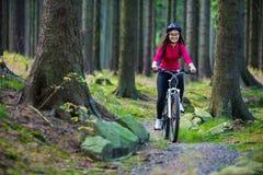 Ciclismo dell'adolescente sulle tracce della foresta Fotografie Stock Libere da Diritti