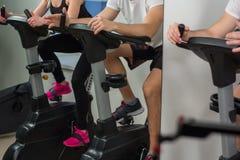 Ciclismo della donna e del giovane nella palestra, esercitante le gambe che fanno le bici di riciclaggio di cardio allenamento Fotografie Stock Libere da Diritti
