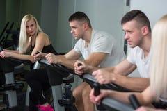 Ciclismo della donna e del giovane nella palestra, esercitante le gambe che fanno le bici di riciclaggio di cardio allenamento Fotografie Stock